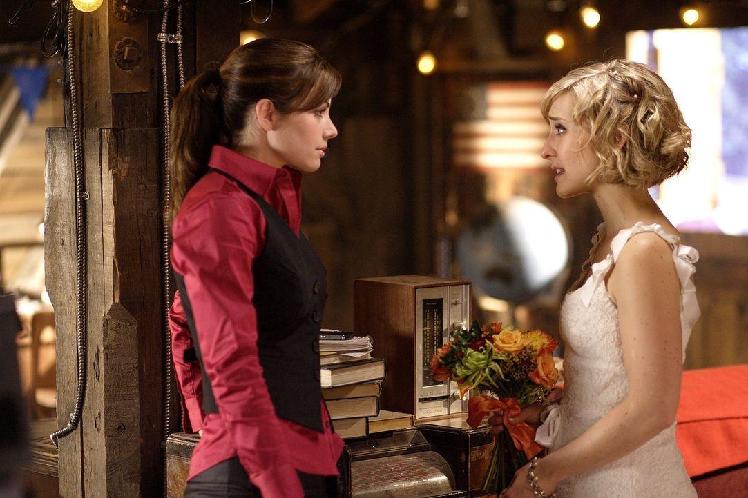 Während Chloe (Allison Mack, r.) heiratet, entwickeln sich bei Lois (Erica Durance, l.) und Clark Gefühle füreinander. Doch Olivers Entdeckung auf K... - Bildquelle: Warner Bros.