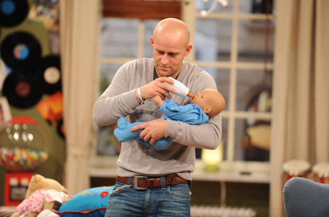 Jürgen (Jürgen Vogel) übt für seine neue Rolle in einem Rosamunde Pilcher-Film den Umgang mit einem Säugling ... - Bildquelle: Jörg Carstensen SAT.1