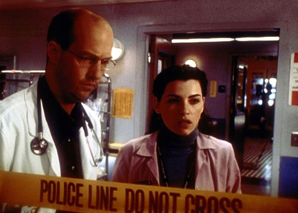 Hathaway (Julianna Margulies, r.) und Greene (Anthony Edwards, l.) schauen zu, wie die Polizei die Spuren eines furchtbaren Blutbades sichert. - Bildquelle: TM+  2000 WARNER BROS.