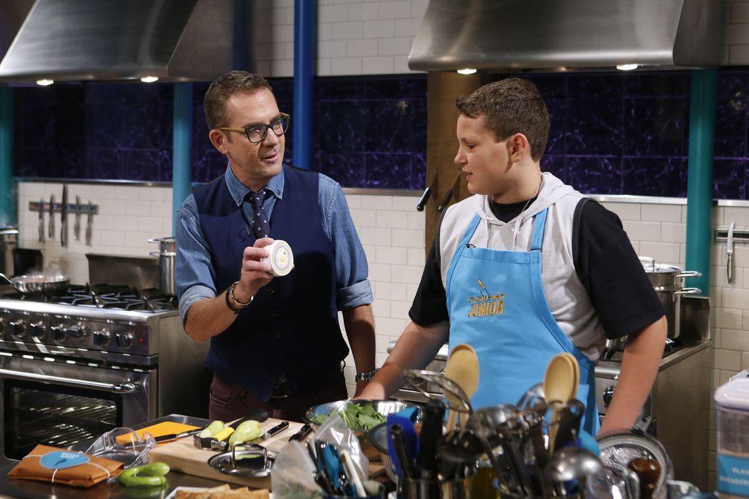 Moderator Ted Allen (l.) ist gespannt, wie sich Micah Riedmann (r.) beim ersten Gang, bei dem die Junior-Köche einen Hammer zum Kochen benutzen müss... - Bildquelle: Jason DeCrow 2015, Television Food Network, G.P. All Rights Reserved