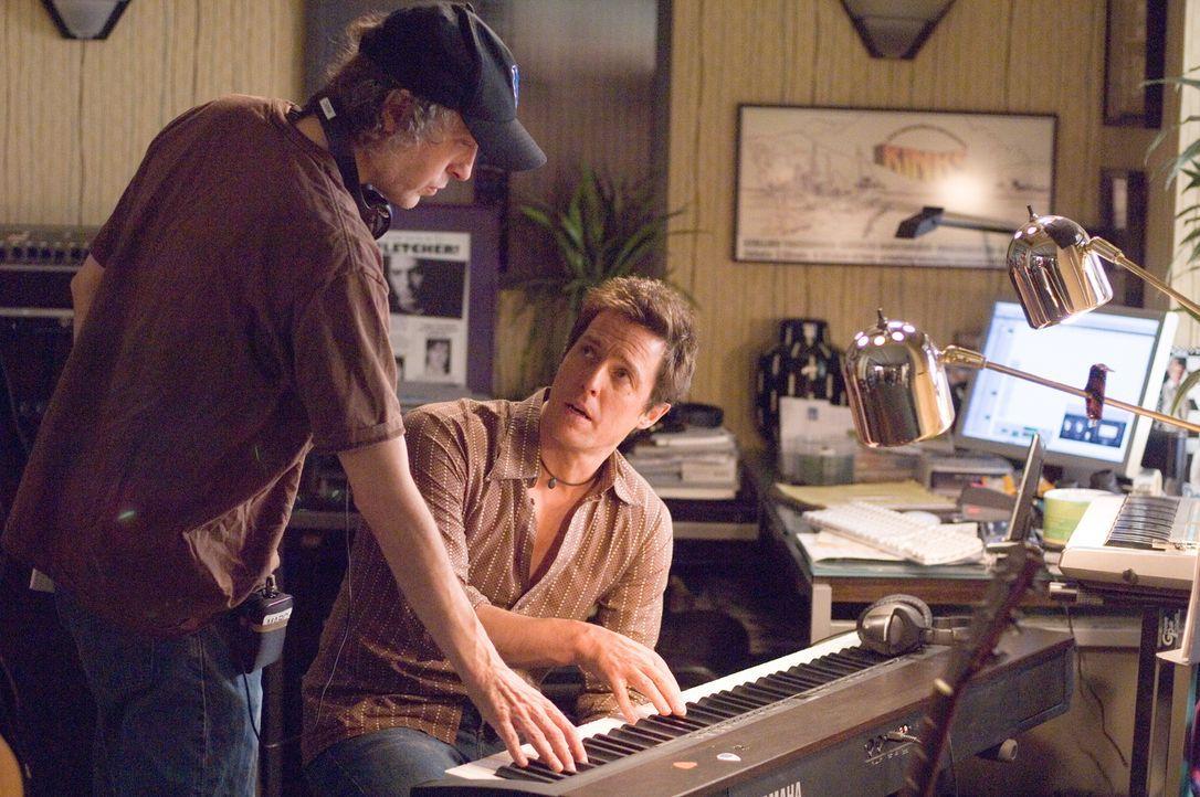 Regisseur Marc Lawrence (l.) bespricht mit Hugh Grant (r.) die nächste Szene. - Bildquelle: Warner Bros.