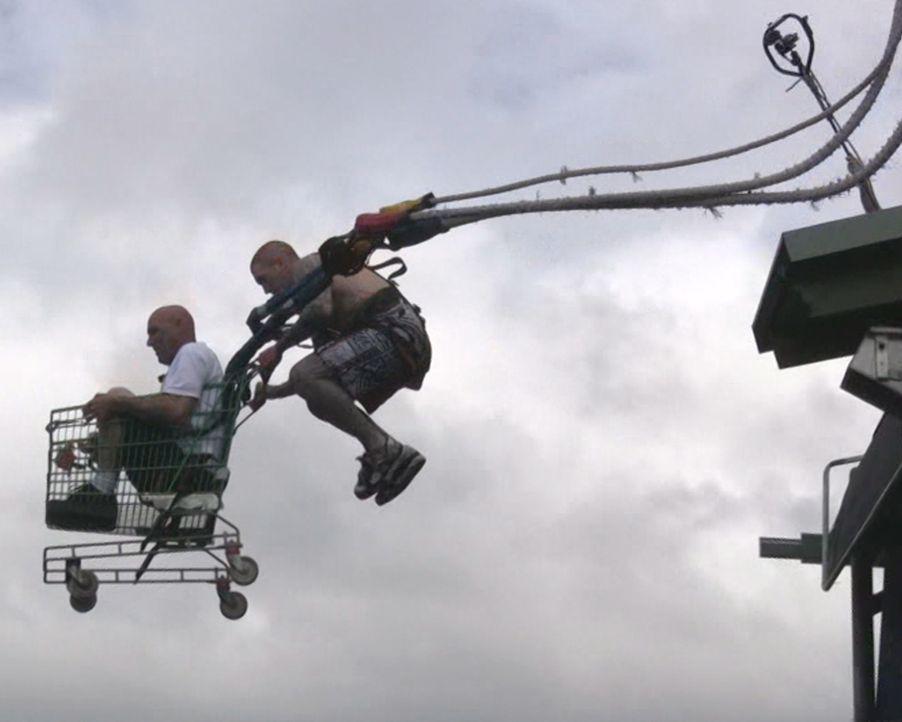 Verrückt und höchst gefährlich: Dana Nicholson (l.) springt in Australien an einem Bungee Jumping-Seil in die Tiefe, während er in einem Einkaufswag... - Bildquelle: 2011, The Travel Channel, L.L.C.