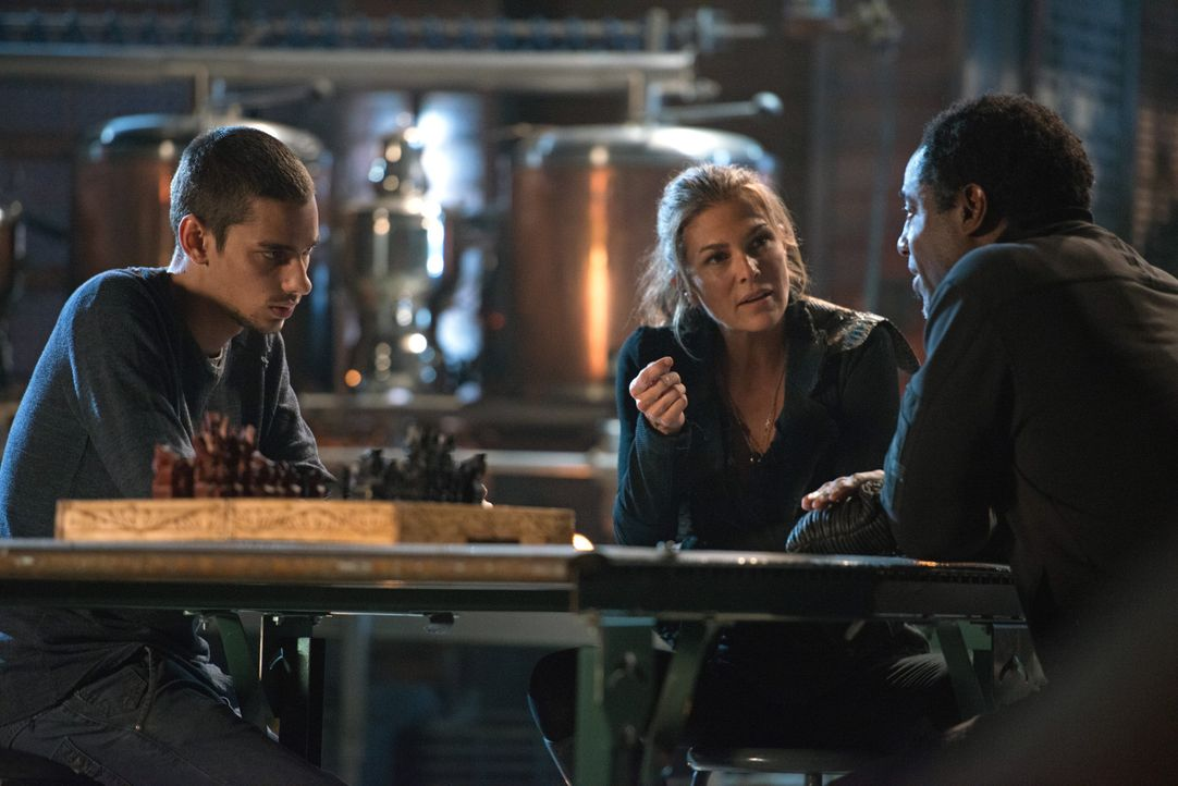 Während Abigail (Paige Turco, M.) Zweifel an dem angeblichen Glücklichmacher hat, überlegt Jasper (Devon Bostick, l.), ob er sich Jaha (Isaiah Washi... - Bildquelle: 2014 Warner Brothers