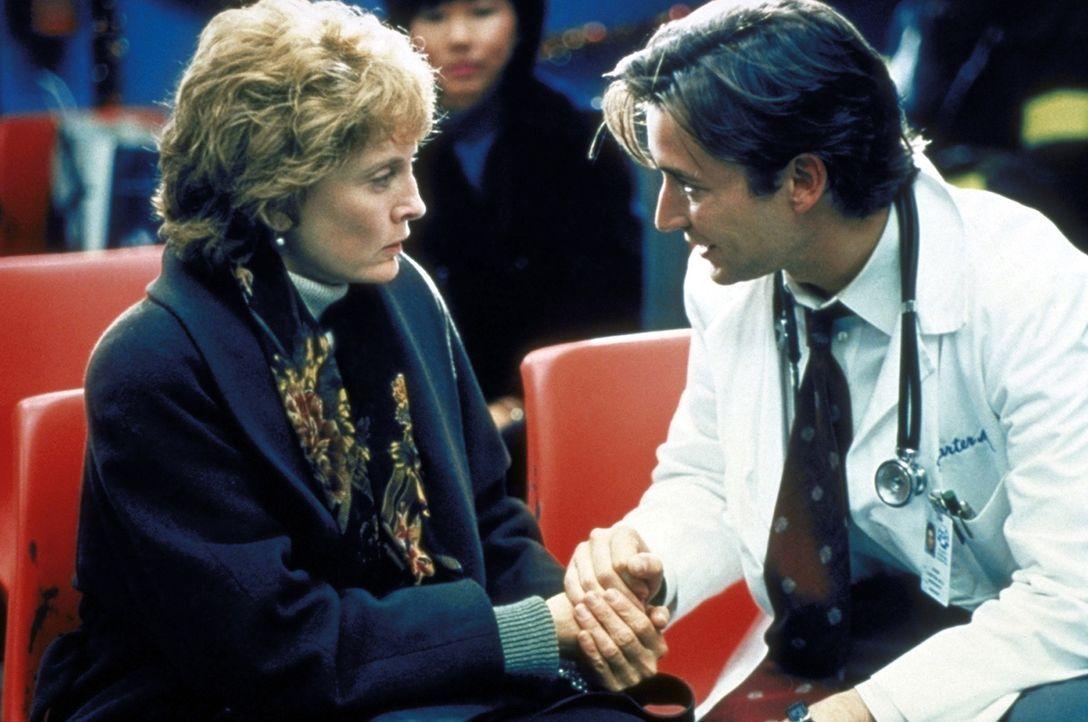 Dr. Carter (Noah Wyle, r.) verspricht Mrs. Richards (Laurie O'Brien, l.), ihren 18-jährigen Sohn noch nicht aufzugeben. - Bildquelle: TM+  2000 WARNER BROS.