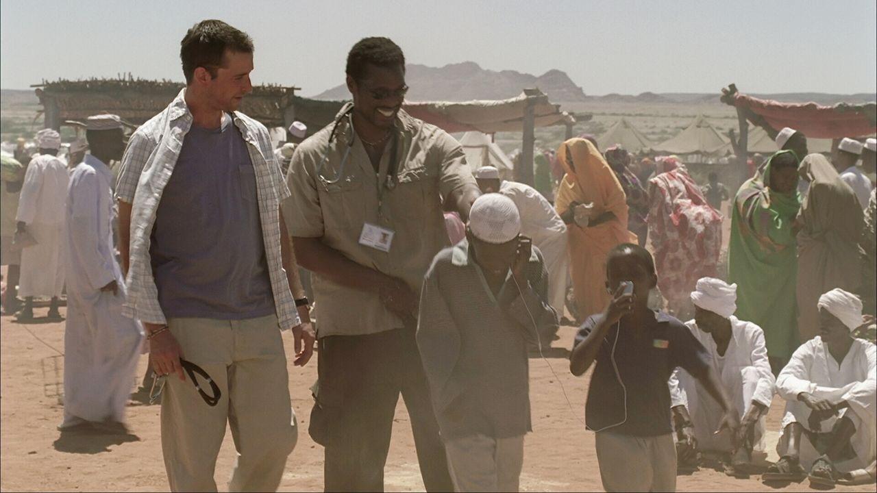 Versuchen kranken und hungernden Einheimischen, die zudem von der Militärpolizei tyrannisiert werden zu helfen: Carter (Noah Wyle, l.) und Dr. Dakar... - Bildquelle: Warner Bros. Television