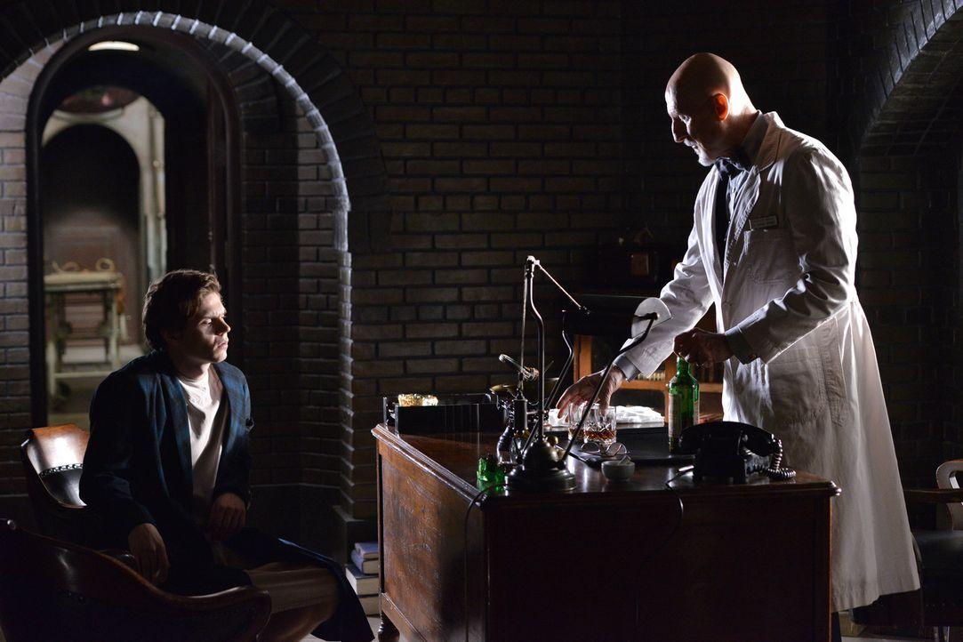Jahr 1964: In seinem Büro teilt Dr. Arthur Arden (James Cromwell, r.) Kit Walker (Evan Peters, l.) mit, dass er die Aliens ebenfalls gesehen hat ...