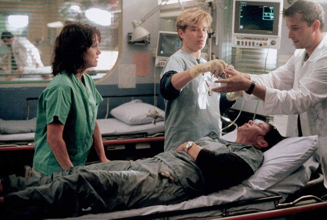 John Carter (Noah Wyle, r.) untersucht Abby (Maura Tierney, liegend) nach der Explosion. Ihre Mutter Maggie (Sally Field, l.) ist besorgt. - Bildquelle: TM+  2000 WARNER BROS.