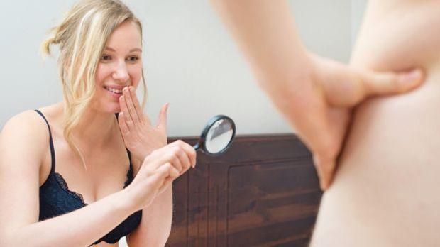 Frau betrachtet Penis durch eine Lupe