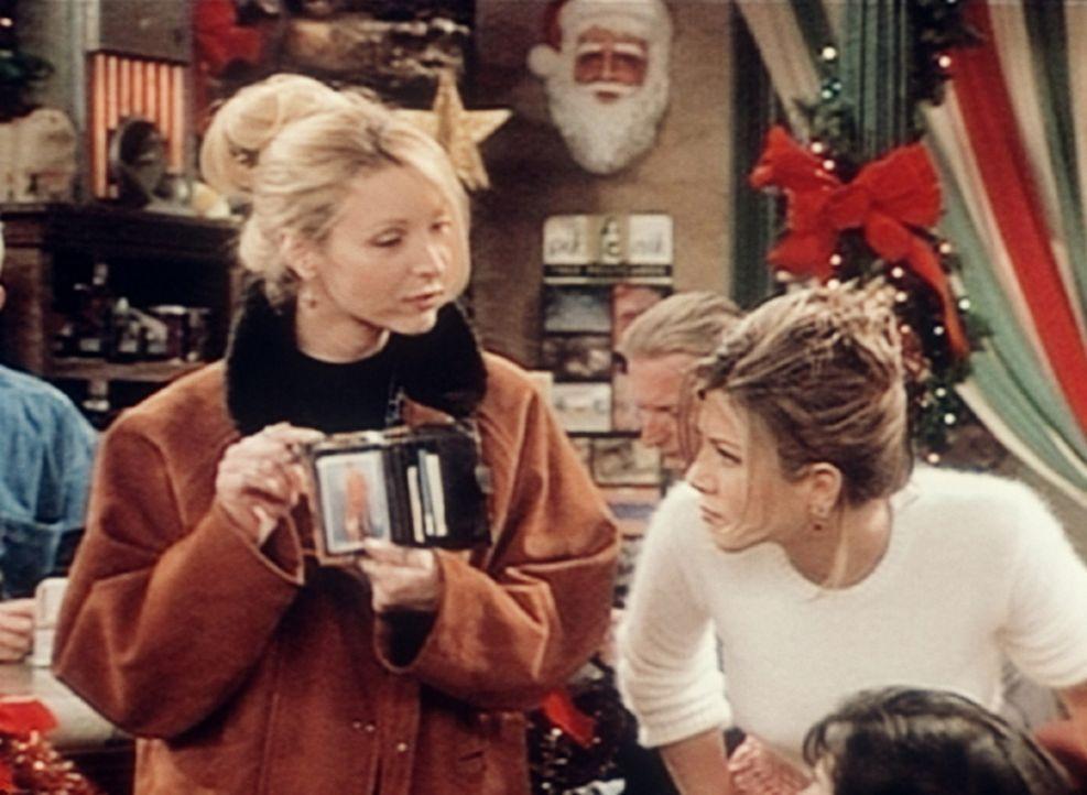 Phoebe (Lisa Kudrow, l.) zeigt Rachel (Jennifer Aniston, r.) ein Bild ihres Vaters. - Bildquelle: TM+  2000 WARNER BROS.