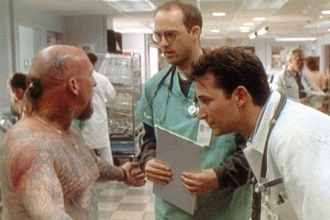 John Carter (Noah Wyle, r.) und Mark Greene (Anthony Edwards, M.) bestaunen den tatowierten Körper eines Patienten (Jeffrey Dean Rosenthal, l.). - Bildquelle: TM+  WARNER BROS.