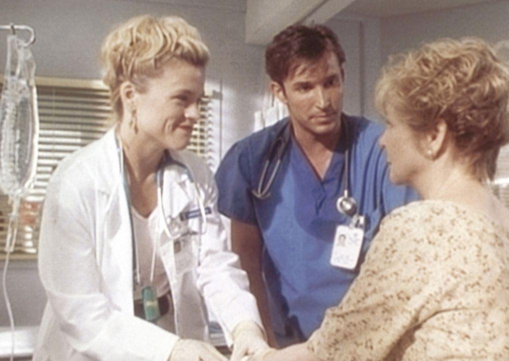 Harper Tracy (Christine Elise, l.) und Carter (Noah Wyle, M.) kümmern sich liebevoll um die Frau eines Patienten. - Bildquelle: TM+  WARNER BROS.