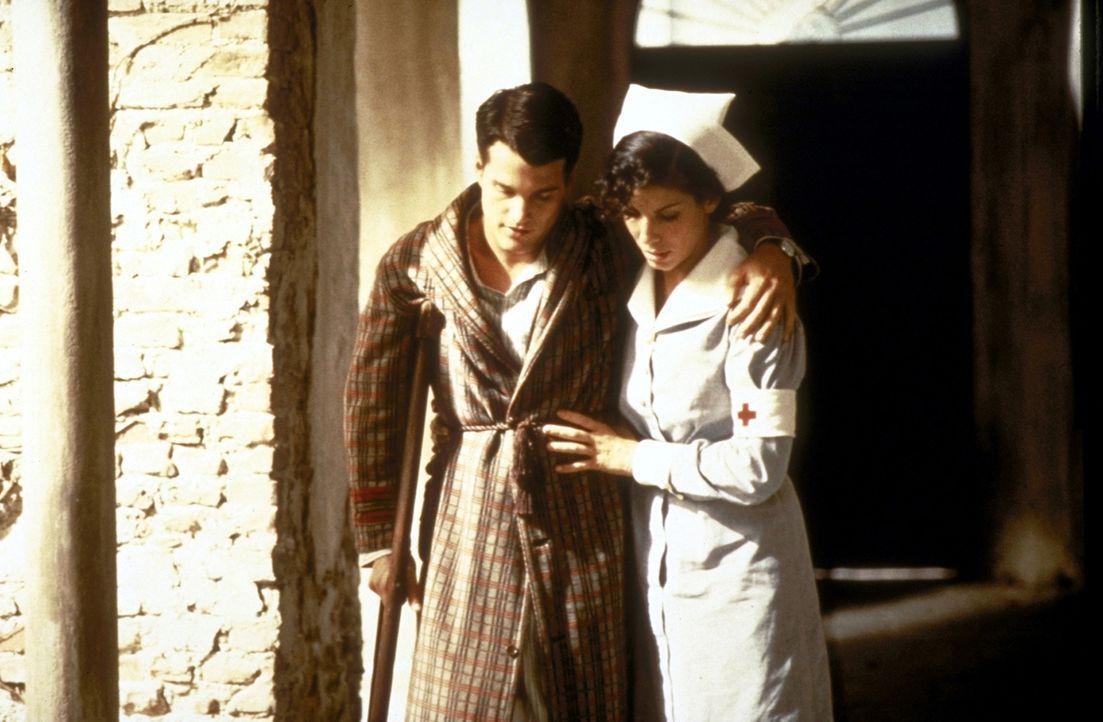 Liebevoll nimmt sich Rote-Kreuz-Schwester Agnes von Kurowsky (Sandra Bullock, r.) des verletzten Ernest Hemingway (Chris O'Donnell, l.) an ... - Bildquelle: Warner Bros.