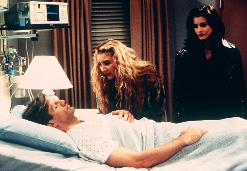 Phoebe (Lisa Kudrow, M.) und Monica (Courteney Cox, r.) umsorgen in der Klinik einen unbekannten Mann, der im Koma liegt. - Bildquelle: TM+  2000 WARNER BROS.