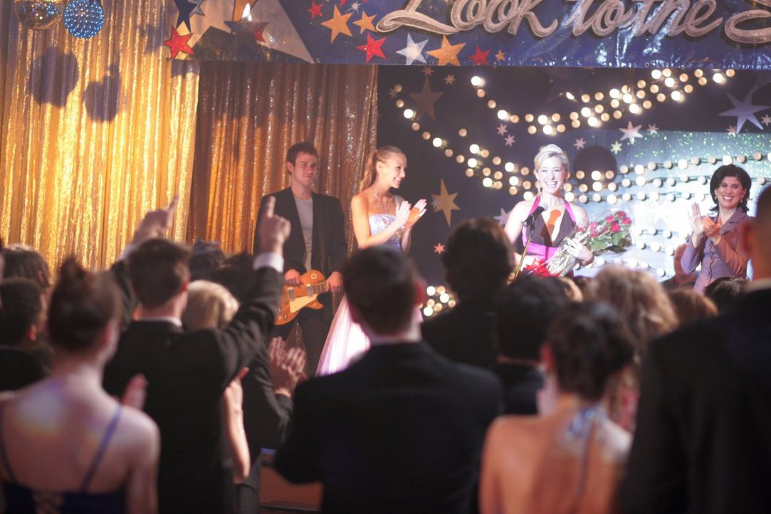 Als Lois die neue Ballkönigin Chloe (Allison Mack, hinten M.) umarmt, wandert Dawns Geist von Lois zu der Ballkönigin ... - Bildquelle: Warner Bros.