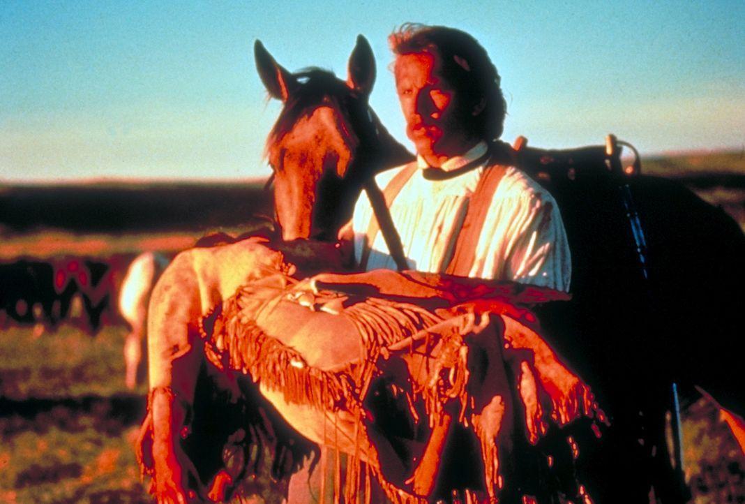 Der friedlichgesonnene Leutnant John Dunbar (Kevin Costner, l.) bringt die verletzte 'Steht mit einer Faust' (Mary McDonnell, r.) in das Lager... - Bildquelle: Orion Pictures Corporation