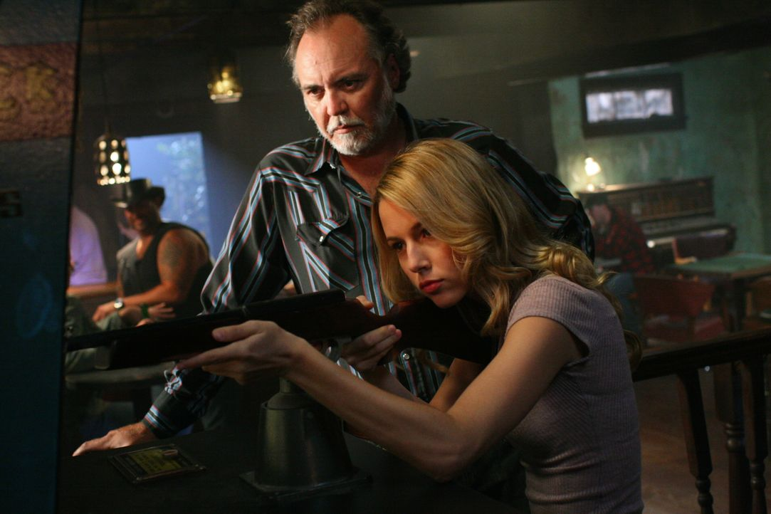 Jo (Alona Tal, r.) zeigt den Gästen in der Bar, wie man ein Ziel anvisiert ... - Bildquelle: Warner Bros. Television