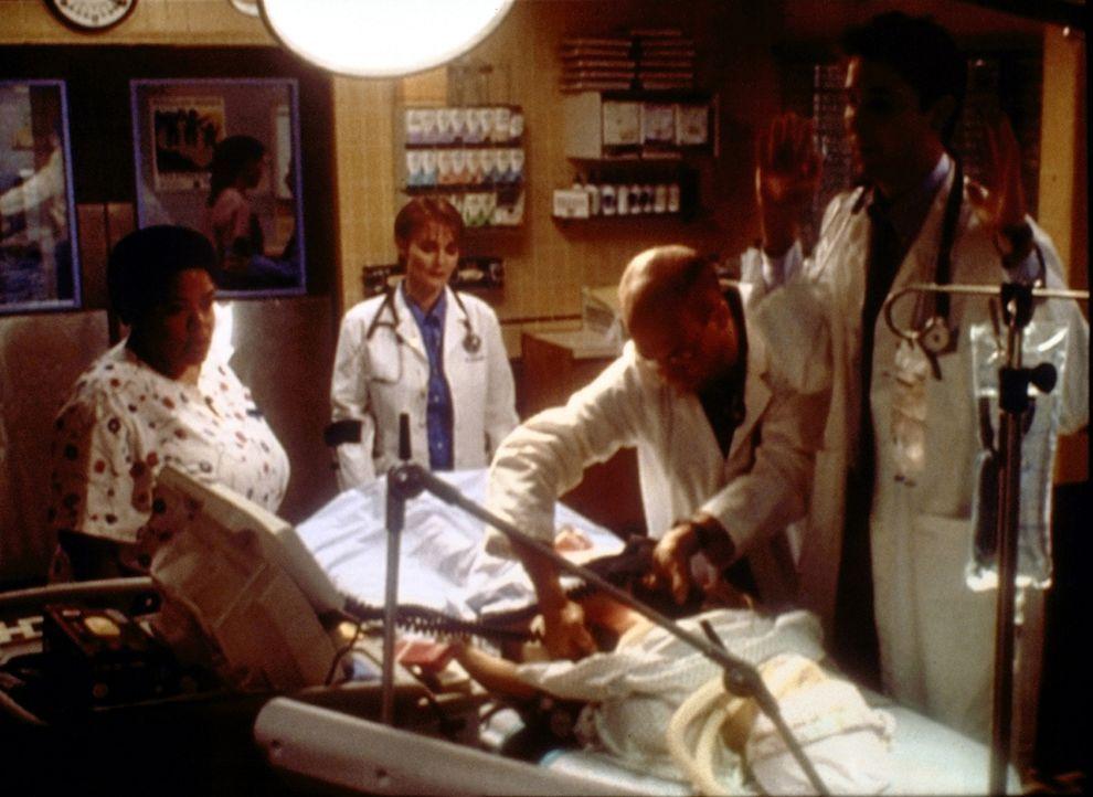 Gegen Anweisung von Dr. Weaver (Laura Innes, 2.v.l.) nimmt Dr. Greene (Anthony Edwards, 2.v.r.) bei einer Krebspatientin Wiederbelebungsversuche vor. - Bildquelle: TM+  2000 WARNER BROS.