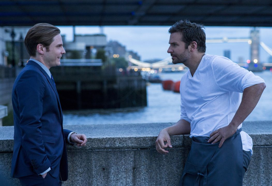 Obwohl Tony (Daniel Brühl, l.) von der Genialität seines Freundes überzeugt ist, willigt er nur ungern ein, Sternekoch Adam Jones (Bradley Cooper, r... - Bildquelle: Alex Bailey 2014 The Weinstein Company. All rights reserved.