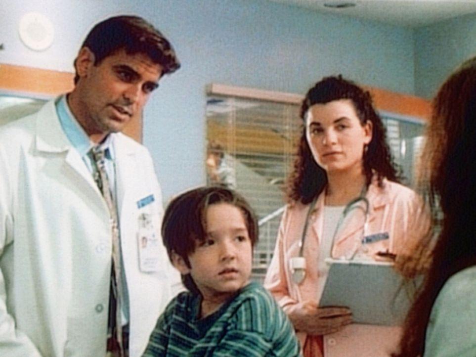 Der kleine Ozzie (Andrew J. Ferchland, M.) wird mit angeblichen Hörstörungen zu Dr. Ross (George Clooney, l.) gebracht. - Bildquelle: TM+  WARNER BROS.