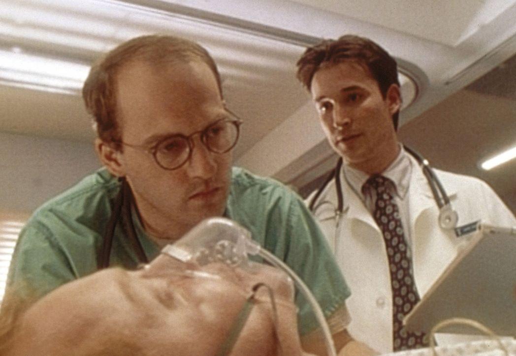 Assistent Carter (Noah Wyle, r.) führt mit Hilfe von Dr. Greene (Anthony Edwards, l.) seine erste Lumbalpunktion durch. - Bildquelle: TM+  WARNER BROS.