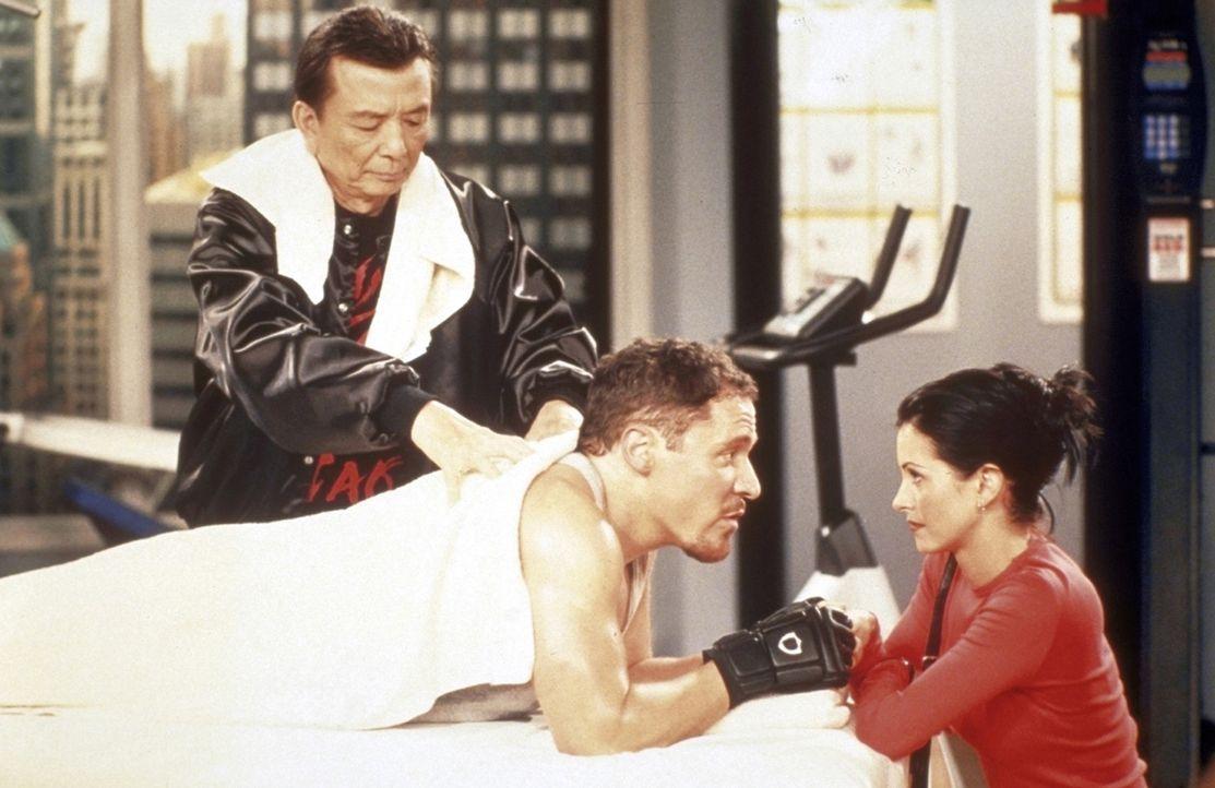 Vor dem Boxkampf spricht Monica (Courteney Cox, r.) ihrem Freund Pete (Jon Favreau, liegend) noch einmal Mut zu. - Bildquelle: TM+  2000 WARNER BROS.