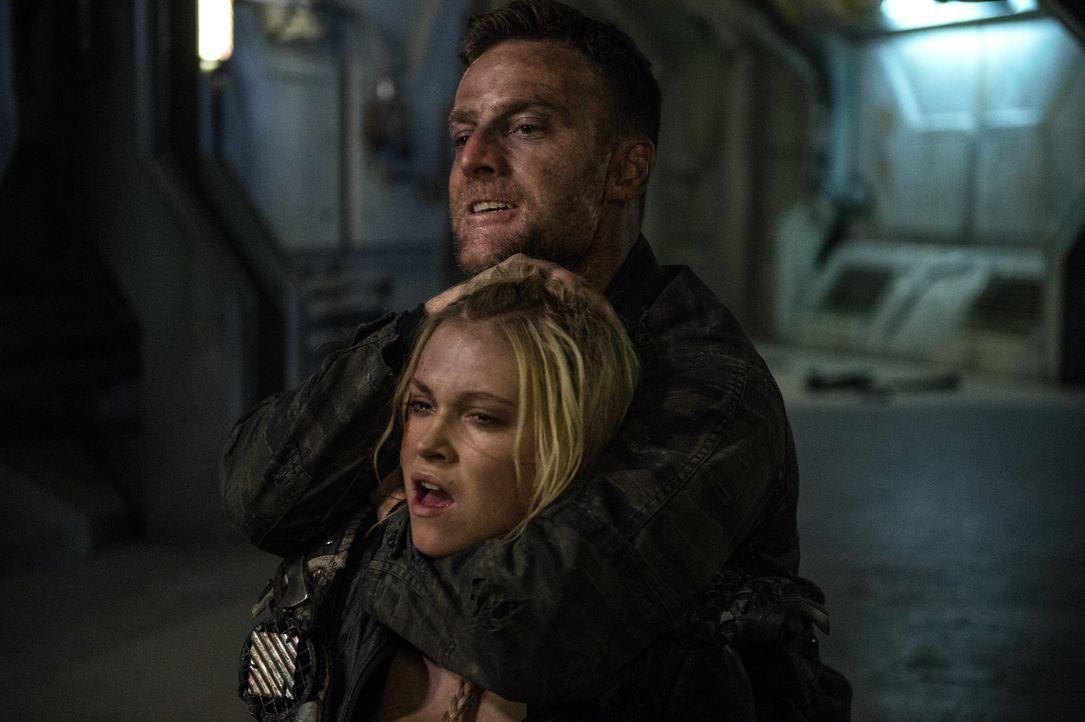 Lt. Carl Emerson (Toby Levins, hinten) will Rache an Clarke (Eliza Taylor, vorne) nehmen. Wird er dafür auch all ihre Freunde töten? - Bildquelle: 2014 Warner Brothers