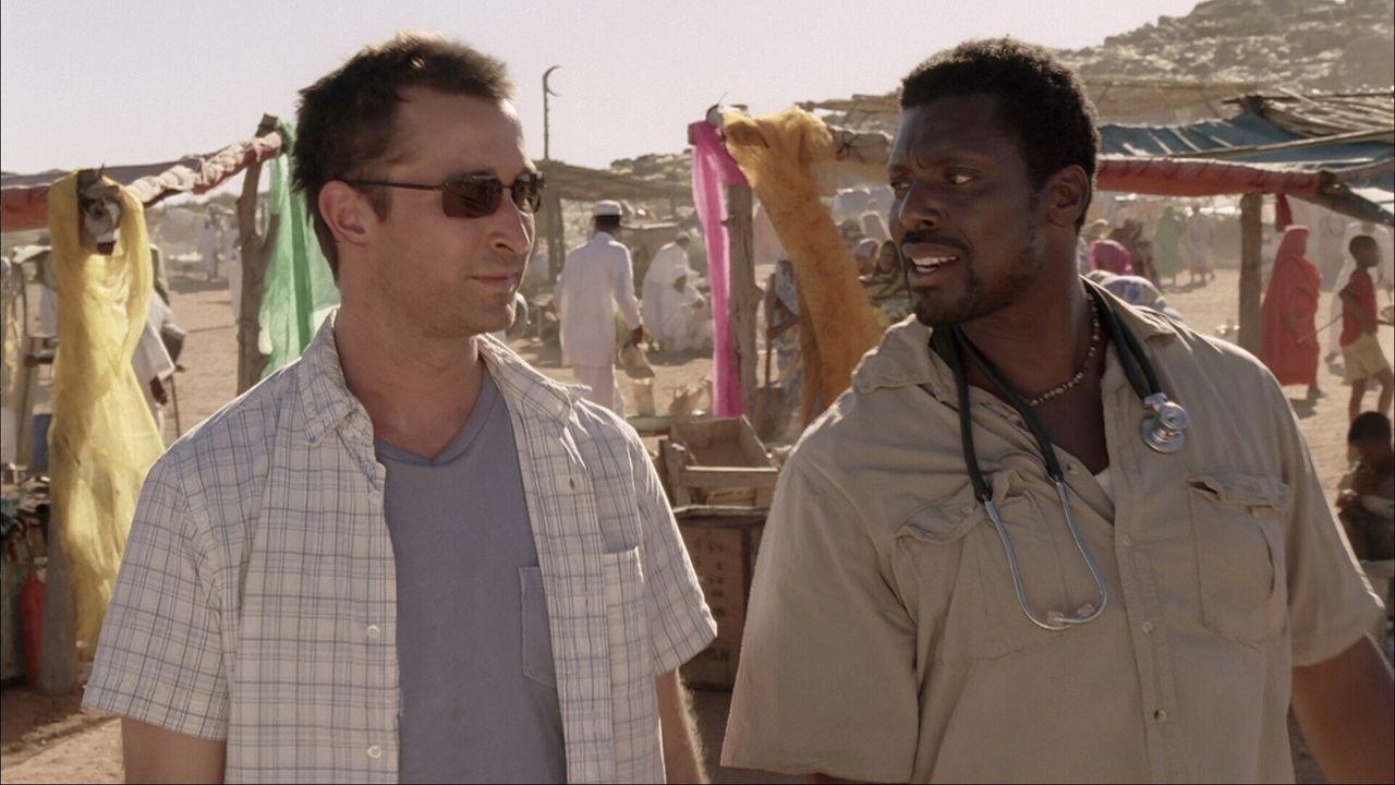 Carter (Noah Wyle, l.) wird angeleitet von dem erfahrenen einheimischen Arzt Dr. Dakarai (Eamonn Walker, r.), der gleichzeitig versucht, seinem neue... - Bildquelle: Warner Bros. Television