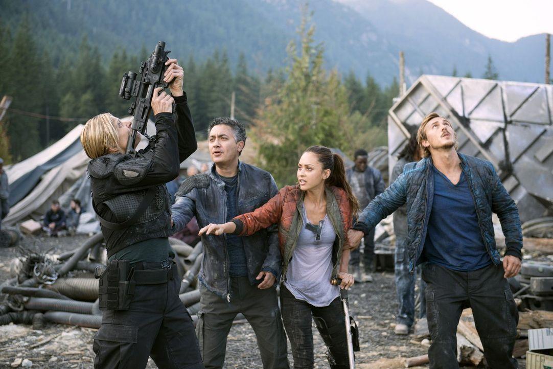 Während Sinclair (Alessandro Juliani, 2.v.l.), Raven (Lindsey Morgan, 2.v.r.) und Wick (Steve Talley, r.) überzeugt von ihrer besonderen Funkmethode... - Bildquelle: 2014 Warner Brothers