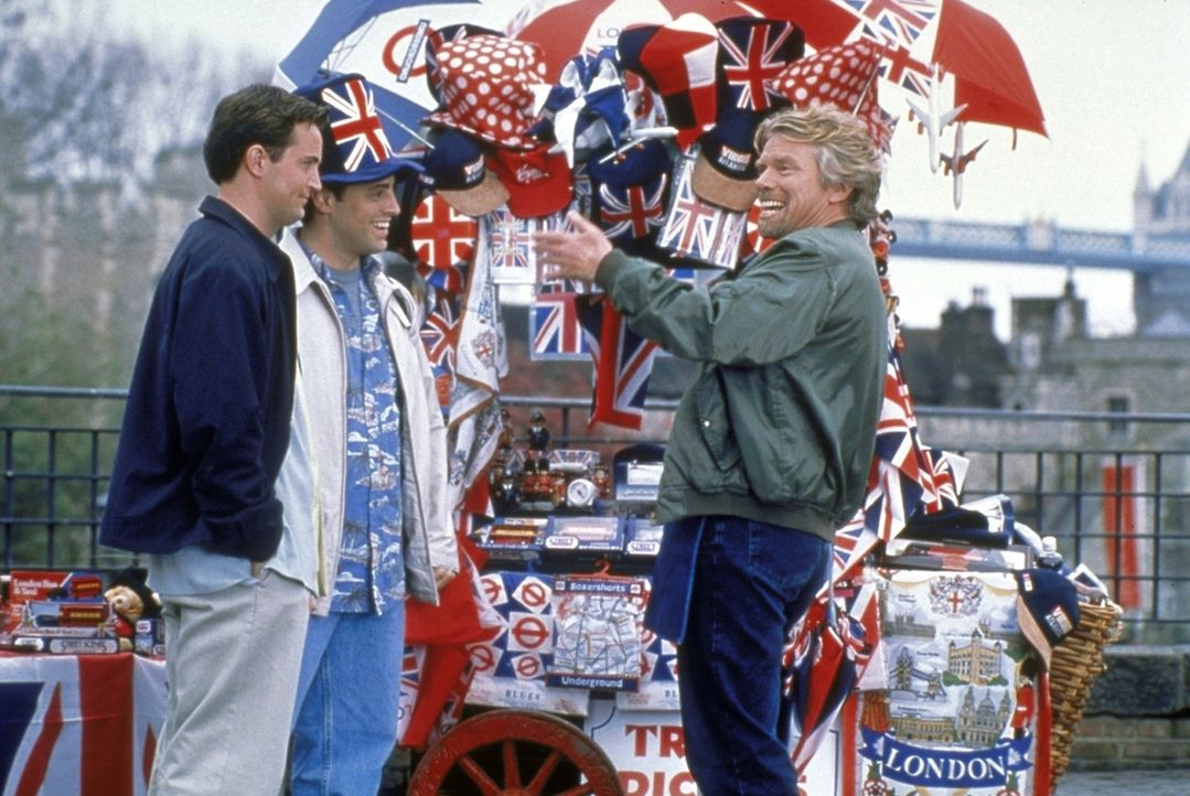 Chandler (Matthew Perry, l.) und Joey (Matt LeBlanc, M.) spielen Touristen in London und lassen sich von einem lustigen, britischen Verkäufer (Rich... - Bildquelle: TM+  2000 WARNER BROS.