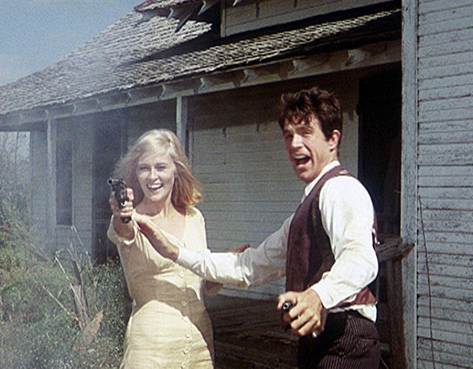 Zusammen mit seiner Gangsterbraut Bonnie (Faye Dunaway, l.) übt Clyde (Warren Beatty, r.) den richtigen Umgang mit der Waffe ... - Bildquelle: Warner Bros.