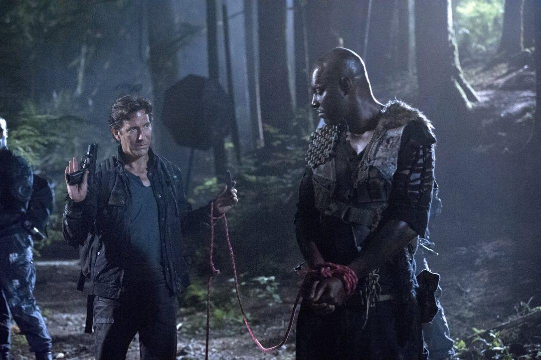 Kane (Henry Ian Cusick, l.) hofft, dass der Grounder Rivo (Colin Lawrence, r.) ihn nicht mitten in eine Falle lockt. Wird er bitter enttäuscht? - Bildquelle: 2014 Warner Brothers