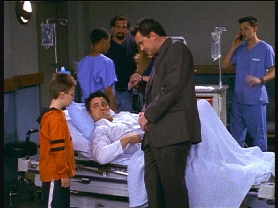 Joey (Matt LeBlanc, liegend) dreht unter Schmerzen eine Szene mit einem Kind, das ständig seinen Text vergisst. - Bildquelle: TM+  2000 WARNER BROS.