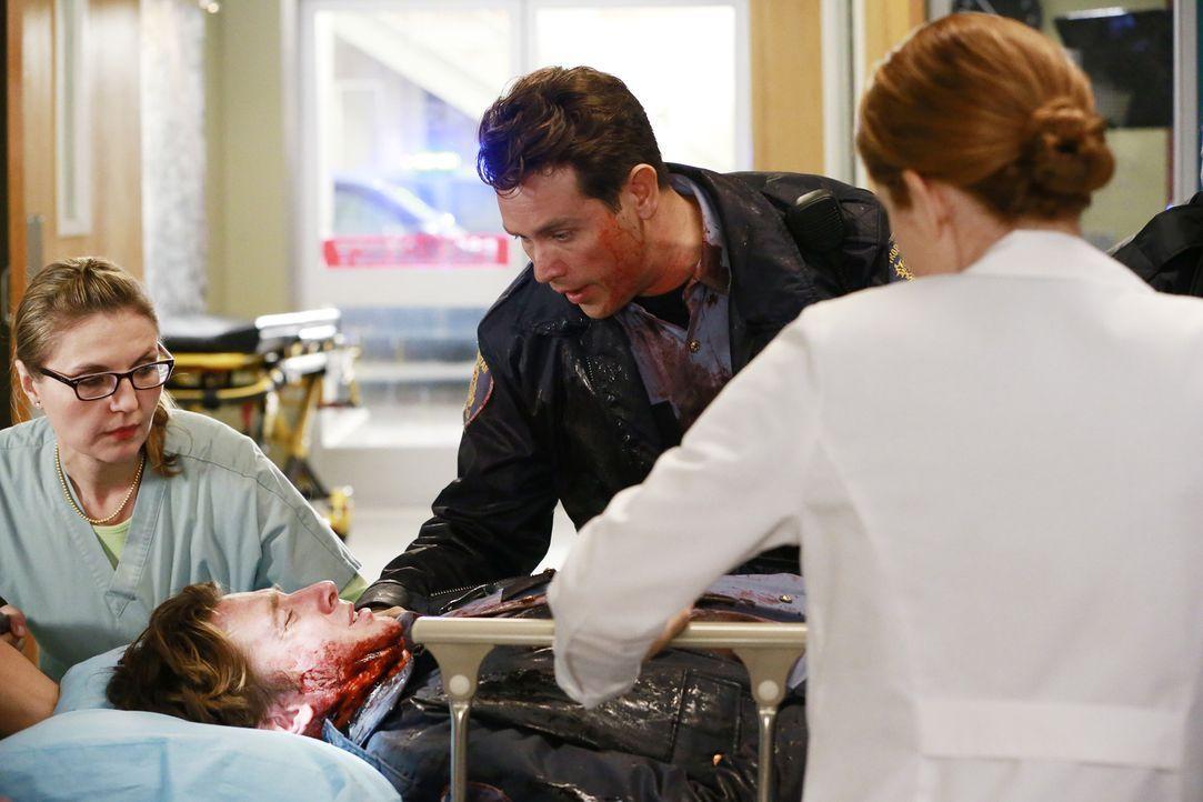 Brett (William Nicol, 2.v.l.) wurde bei einem Banküberfall schwer verletzt. Während sein Kollege Dan (Kevin Alejandro, 2.v.r.) sehr besorgt ist, küm... - Bildquelle: ABC Studios