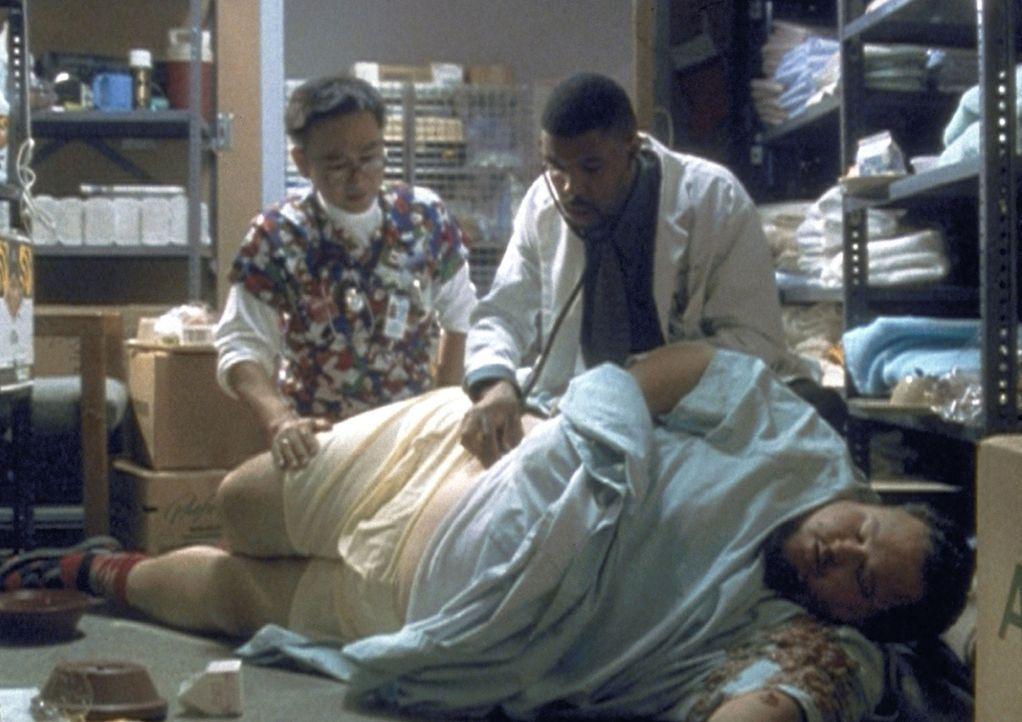 Takata (Gedde Watanabe, l.) und Dr. Benton (Eric LaSalle, M.) finden ihren übergewichtigen Patienten in einem äußerst kritischen Zustand vor. - Bildquelle: TM+  2000 WARNER BROS.