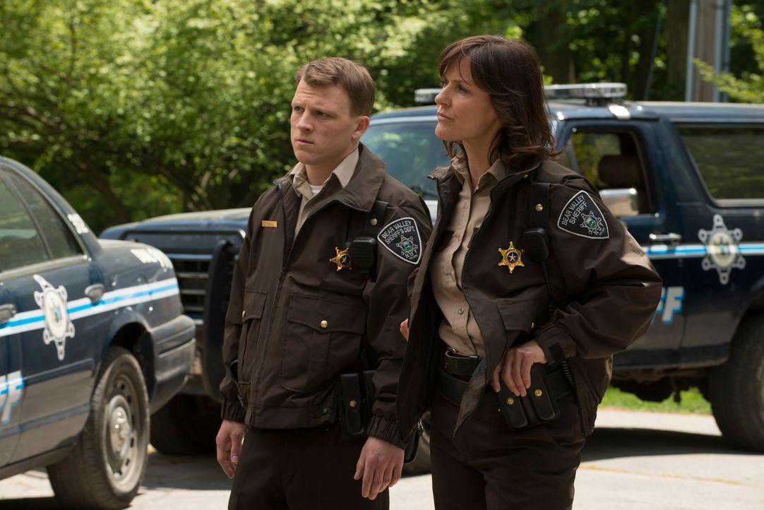 Sheriff Morgan (Fiona Highet, r.) und ihr Kollege Deputy O'Neil (Rogan Christopher, l.) glauben, dass in Stonehaven irgend etwas Seltsames vor sich... - Bildquelle: 2014 She-Wolf Season 1 Productions Inc.