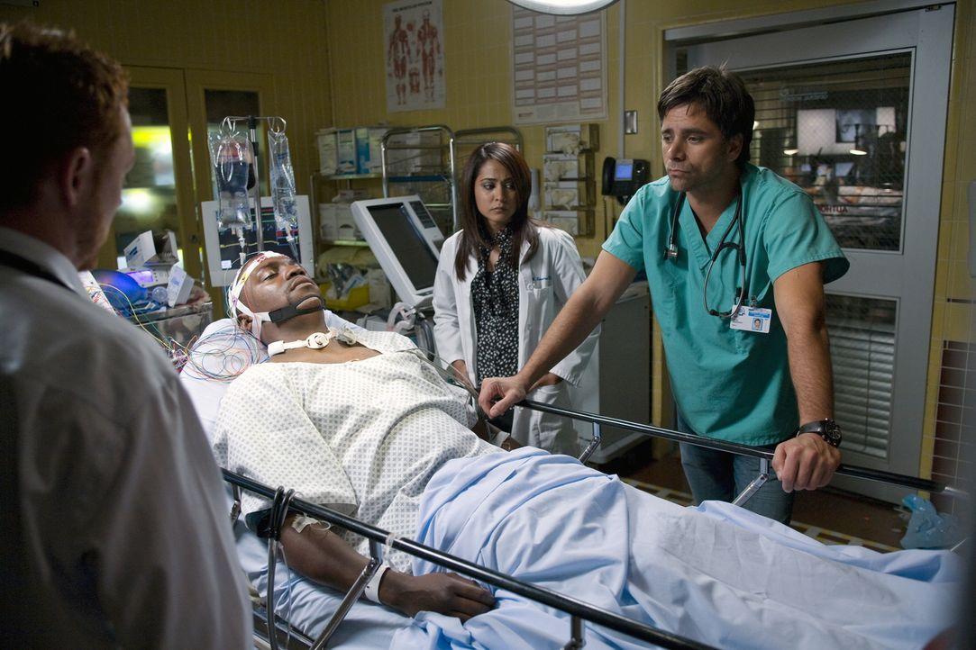 Versuchen alles Menschenmögliche, um ihren Freund und Kollegen Dr. Gregory Pratt (Mekhi Phifer, liegend) zu retten: Dr. Archie Morris (Scott Grimes... - Bildquelle: Warner Bros. Television